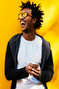Young black male wearing sun glasses and laughing with a mobile phone in hand.