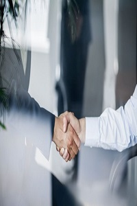 Hands of two people wearing formal work clothes shaking