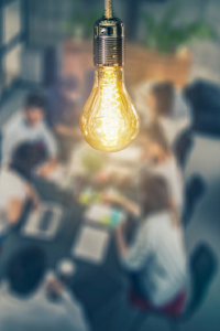 out of focus image of people sat around a table in a business meeting. Bulb shines in the foreground