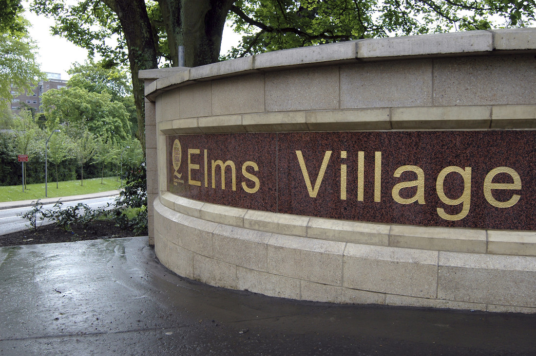Elms Village entrance sign, gold lettering on brown