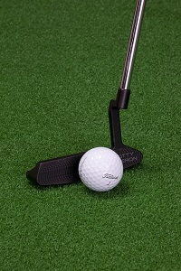 Putter and golf ball and green background