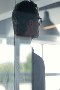 man wearing glasses facing away, viewed through reflective glass