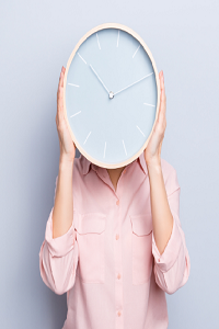 Person holding large clock face in front of their head, they are wearing a salmon coloured shirt