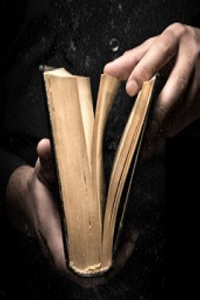 Cropped hands opening a book against black background