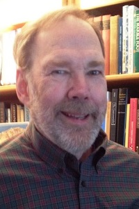 Head shot of Professor James Turner (with beard) in front of book shelf