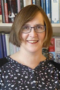 Professor Moyra Haslett smiling, bookcase with books behind