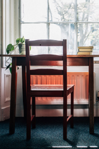 Chair, books and plant on top of a desk facing large window