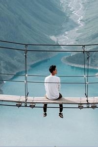 Man sitting on a rope bridge looking out over lake and valley