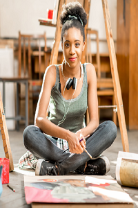 Young lady sat cross legged in a art studio surrounded by art and easels