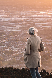 Woman viewing cityscape from mountain top