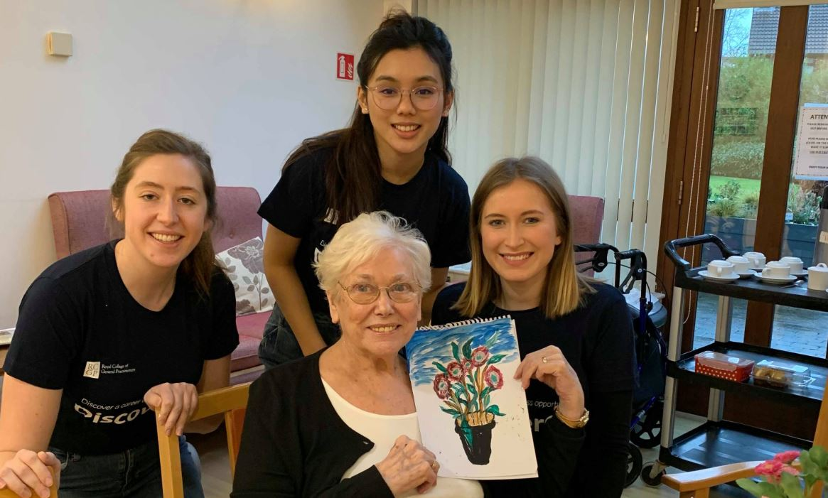 Three students from GP Society with elderly patient