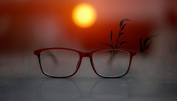 Pair of reading glasses on table with sun setting in background