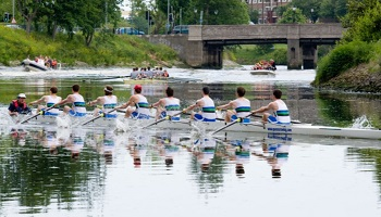 Coxed eight rowing on River Lagan with second crew and suppoprt boats in background