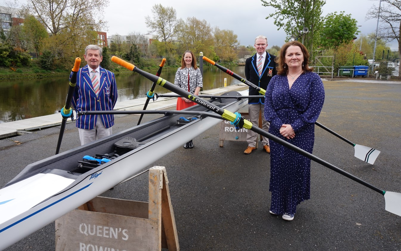 Four people, two men and two women, standing beside a rowing boat by the river