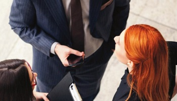 Overhead image of two business women talking to a man