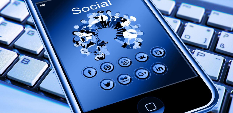Mobile phone displaying various social media logos sat on top of desktop keyboard