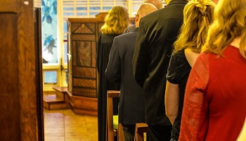Women and men with backs to camera gathered in church