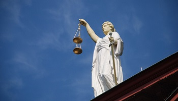 Justice, blindfolded, with scales in one hand and sword in other against blue sky background