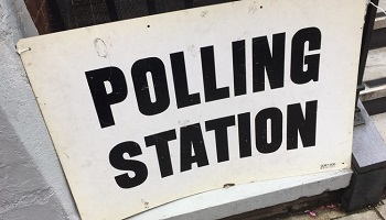 Polling station sign on railings outside building