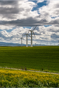 Green fields with wind turbines, low clouds and some blue sky