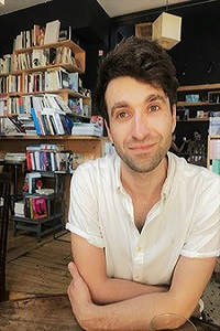 Tom Western wearing white short sleeved shirt with book shelve in the background